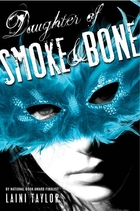 Cover art for Daughter of Smoke & Bone, featuring a white person wearing a brilliantly blue feathered mask. The cover is in black and white aside from the mask.