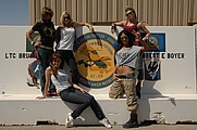 Author photo. The Pussycat Dolls pose for the troops in front of an Operation Iraqi Freedom unit seal on Camp Buehring, Kuwait, on Mar. 10, 2008 / U.S. Army photo by PFC. Sarah De Boise