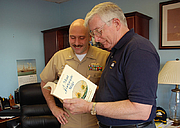 Author photo. Martin signs a copy of his book <i>A Most Fortunate Ship</i> for Cmdr. William A. Bullard III. U.S. Navy photo by Mass Communication Specialist 1st Class Eric Brown (navy.mil)