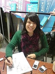 Author photo. Aimee signing at a book fair