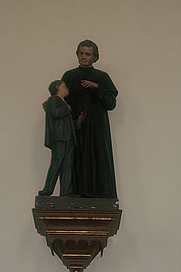 Author photo. St. John Bosco and Youth, Franziskanerkloster Innichen, Innichen, S. Tyrol, Italy.  Image by user JJ55 / Wikimedia Commons.