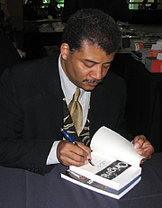 """Author photo. Neil deGrasse Tyson siging a copy of his book """"Origins"""". Portrait taken at JREF's TAM6, The Amazing Meeting. Photo by Wikimedia Commons user Sgerbic"""