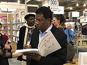 """Author photo. Dany Laferrière au Salon du livre de Montréal 2018 By ActuaLitté - Dany Laferrière, CC BY-SA 2.0, <a href=""""https://commons.wikimedia.org/w/index.php?curid=74757392"""" rel=""""nofollow"""" target=""""_top"""">https://commons.wikimedia.org/w/index.php?curid=74757392</a>"""