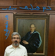Author photo. George A. Kiraz in front of the portrait of Philip Hitti at Princeton University