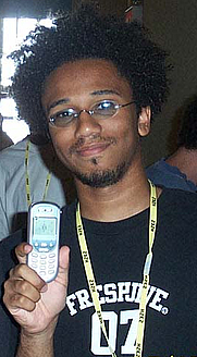 """Author photo. """"Aaron McGruder, at the 2002 Hackers On Planet Earth hacker con"""" by Rob Vincent."""
