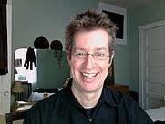 Author photo. Me smiling at my desktop