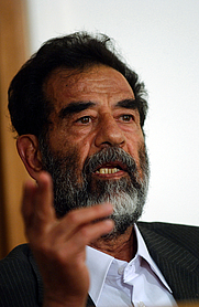 Author photo. Former President of Iraq, Saddam Hussein, makes a point during his initial interview by a special tribunal, where he is informed of his alleged crimes and his legal rights, 7/1/2004.
