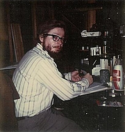 Author photo. Ted Johnstone (David McDaniel) at his desk, writing.