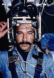 Author photo. Payload specialist Wubbo J. Ockels prepares to lower the eye-gear portion of the vestibular sled helmet for a test on the busy sled. The scientist has sensors on his face and forehead for system monitoring. (nix.ksc.nasa.gov)