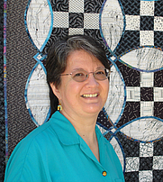 Author photo. Scarlett Rose shown in front of her quilt, the Knotwork Nine Patch.