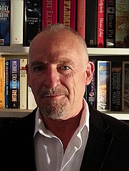 Author photo. Ken Grace at home with his books