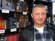Author photo. Me at a the Mysterious Galaxy holiday party, here in beautiful San Diego, posing in front of my books. Because you just gotta do that, right? :)