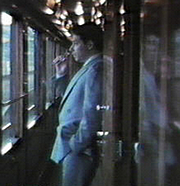 """Author photo. American author, journalist and poet David M. Alexander having a smoke on the Venice-Simplon Orient Express. By Datawatch. - Own work., Public Domain, <a href=""""https://commons.wikimedia.org/w/index.php?curid=14515146"""" rel=""""nofollow"""" target=""""_top"""">https://commons.wikimedia.org/w/index.php?curid=14515146</a>"""
