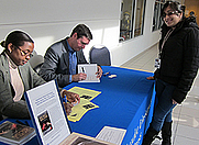 Author photo. Signing copies of SECRET SIGNS at Gallaudet University, Oct 2011.